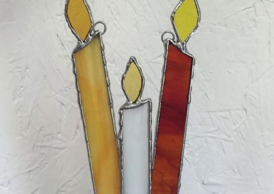three lit Winterfest candles, white, yellow, and reddish orange