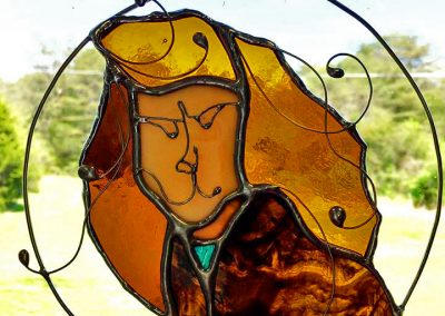 A circular stained glass suncatcher - Vincent's face