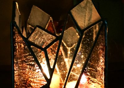 A votive candle holder designed with cavern crystals
