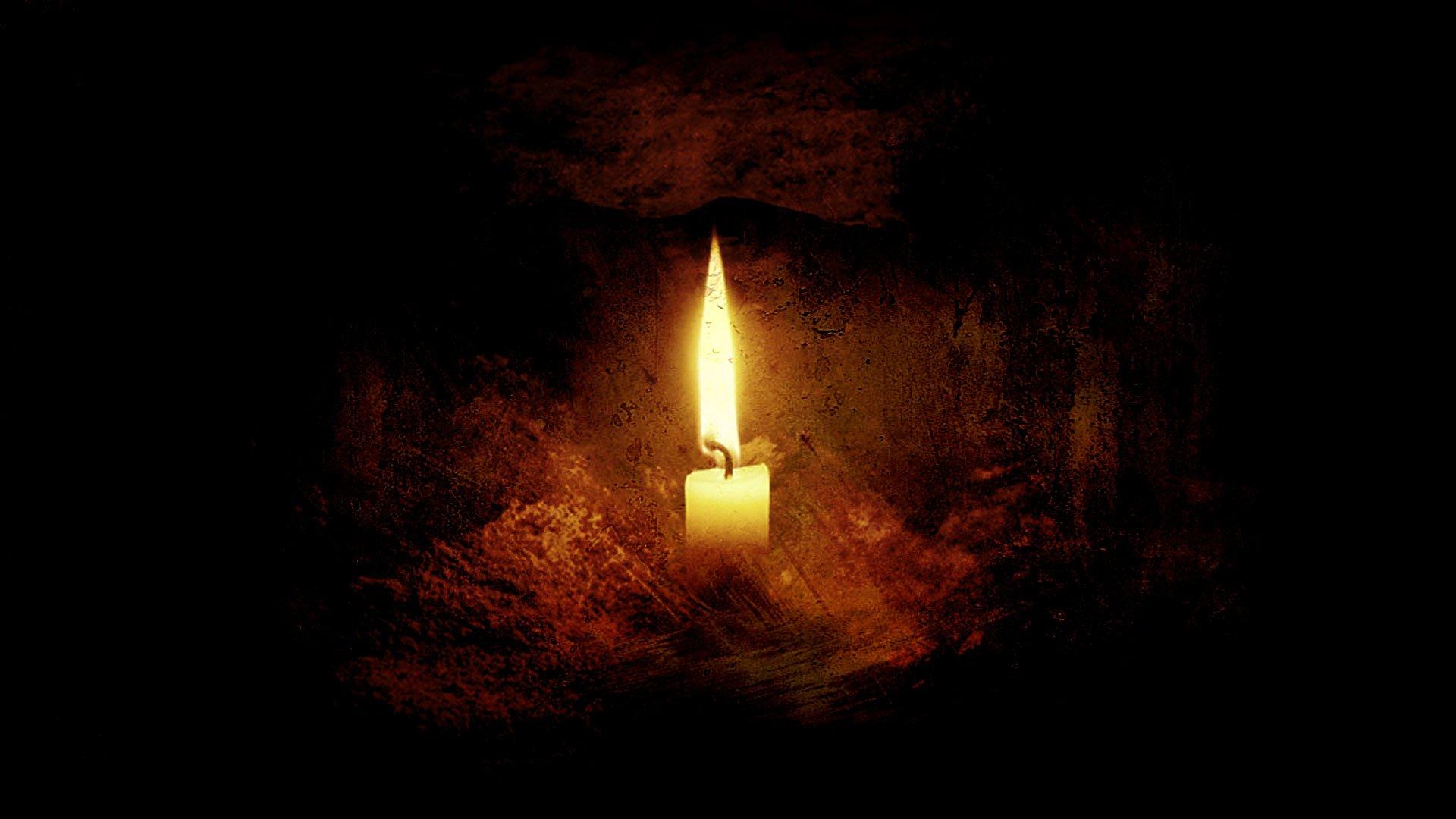 a single lit candle set on a rocky ledge