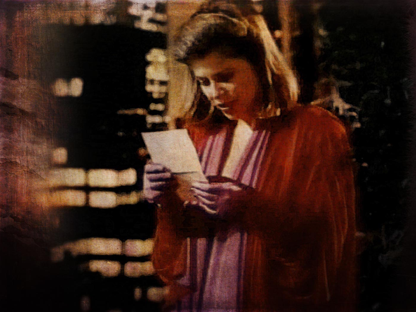 Catherine on her balcony, reading a note from Vincent and smiling