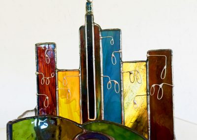 stained glass candle landscape - the tunnel entrance and behind it the high rises of the city