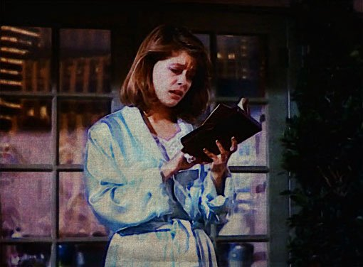 Catherine on her balcony, reading from her book of sonnets, a look of concern on her face