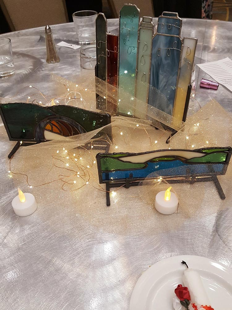 The stained glass centerpiece set up on the banquet table with led candles, fairy string lights and netting