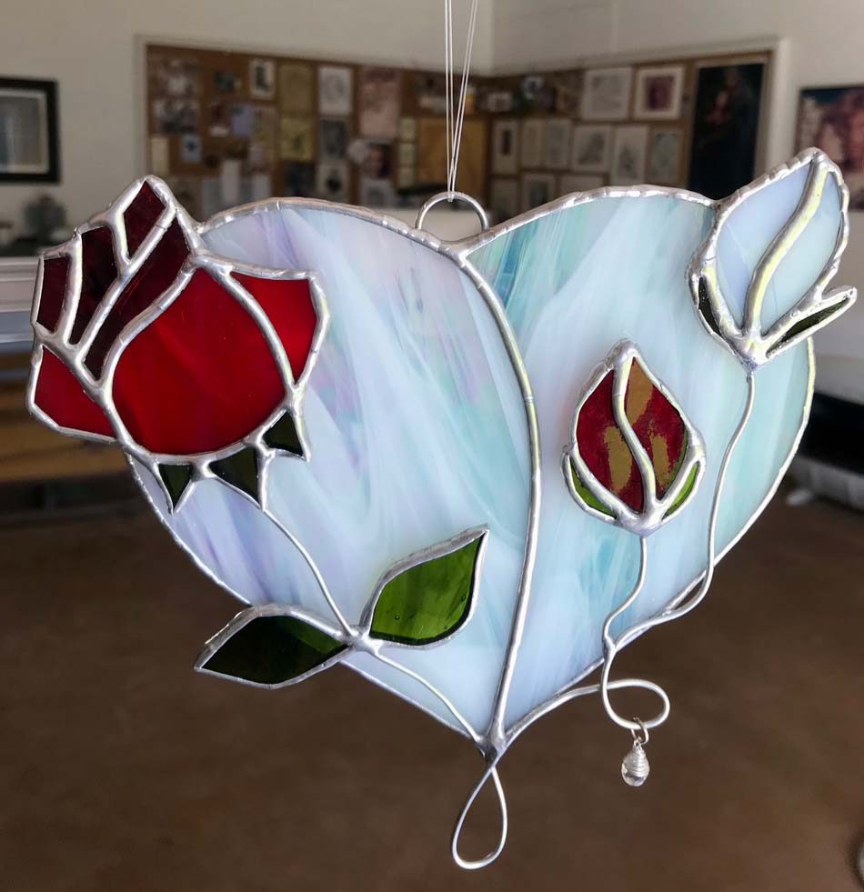 A stained glass heart with an overlay of roses, red and white
