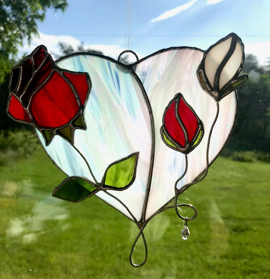 A stained glass sun catchers - a white heart with red and white roses affixed to it