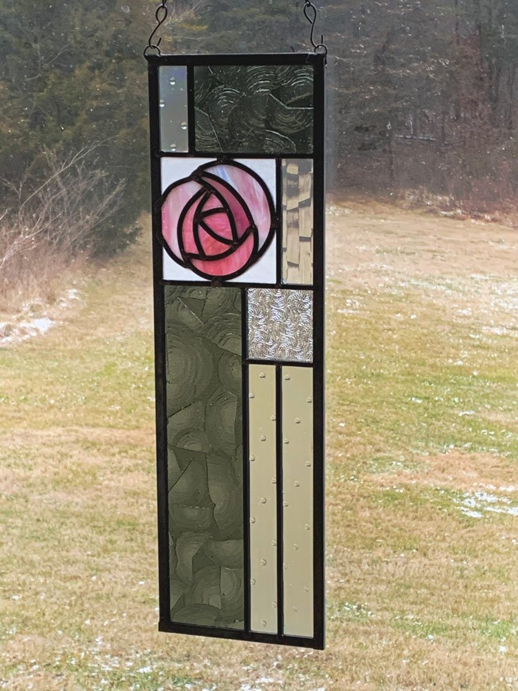 A pink rose with gray and clear textured glass